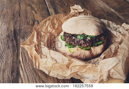 Classic american fast food background. Burger whole grain bun with grilled on barbecue ground beef cutlet on wood in craft paper. Hamburger with fresh vegetables composition. Filtered