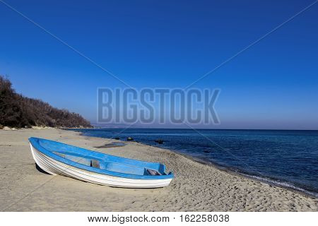Day landscape of lonely boat on the beach
