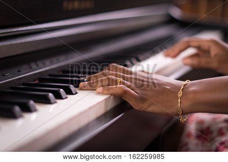 Dark Skin Female Hands Playing Piano Keyboard
