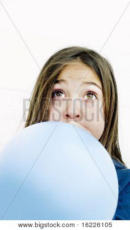 Little girl blowing up a balloon