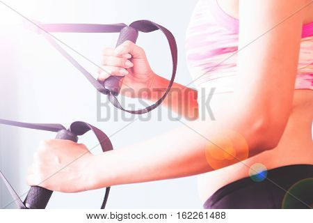 Bodybuilding. Strong fit woman exercising with TRX strap.