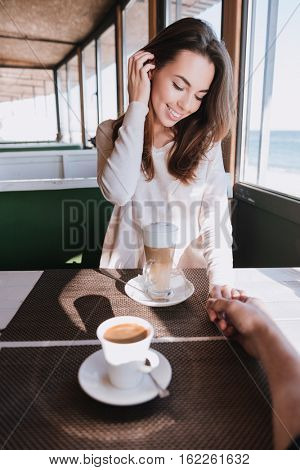 Vertical image of woman on date with man sitting by the table with coffee in cafe near the sea. First-person view