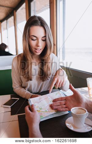 Vertical image of Man and girl sitting by the table with map in cafe near the sea on date. First-person view