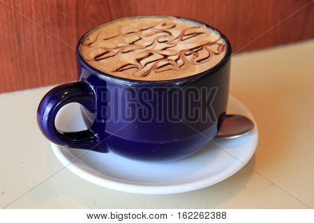 Big blue mug filled with hot,steaming latte that has been drizzled with chocolate syrup