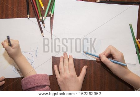 Children draw with crayons on white paper.