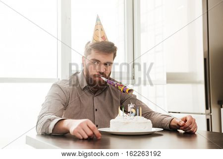 Image of angry bearded father of birtday little boy sitting in kitchen while look aside.