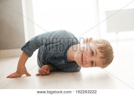Photo of little happy boy lies on the floor while look at the camera.