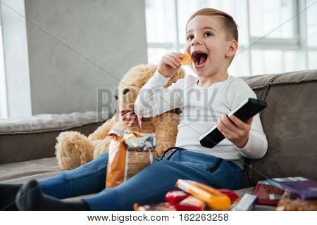 Image of happy boy sitting on sofa with teddy bear at home and watching TV while eating chips. Holding remote control.