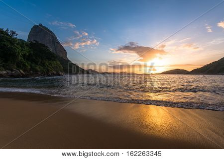 Beautiful Sunrise in the Beach with Few Clouds in the Sky, Sugarloaf Mountain in the Horizon, and Reflection of Sun in the Sand, Rio de Janeiro, Brazil