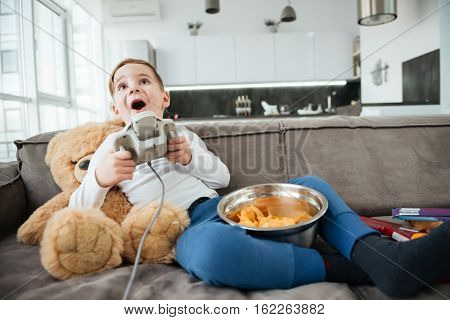 Image of little boy on sofa with teddy bear at home playing games by console while eating chips. Holding joystick.