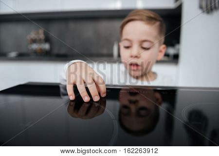 Picture of dangerous situation in the kitchen. Child playing with electric oven.