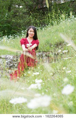 Woman In Flower Field Wearing Red Dress
