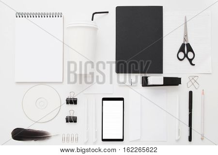 Black and white office stuff collection flat lay. Top view on set of stationery with smartphone and coffee to go paper cup. Modern life, communication, time-management, technologies concept