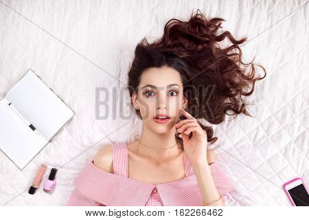 Serious woman lying on bed top view. Beautiful brunette in pink thinking about life surrounded by female accessories, free space. Idea, inspiration, philosophy, creative concept