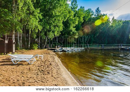 Beautiful deserted sandy beach of a forest lake with deckchairs and moored boats in solar patches of light