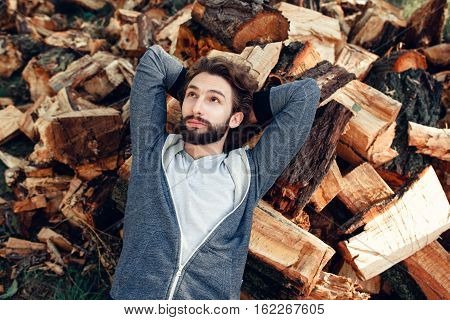 Man having rest on pile of wood top view. Young guy dreaming on bunch with firewood. Hard work, relax, handyman, country lifestyle concept