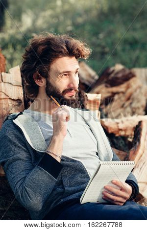 Thinking guy with notebook on pile of wood. Young man speculating about building, repair, to do list, shopping list, leaning on firewood bunch.