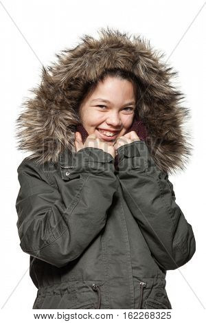 Little girl wearing winter coat with the fur hood, isolated on white background