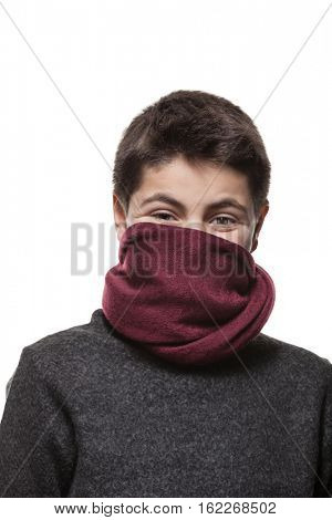 Face of a teen boy hidden by a red scarf, portrait in studio