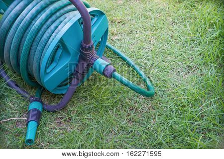 Garden hose on the green grass in garden