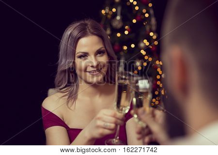 Young attractive couple enjoying romantic Christmas dinner drinking champagne and making a toast