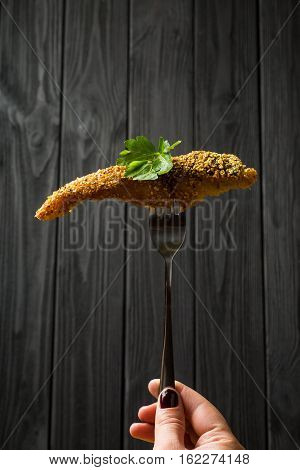 Pieces of fried Fish on a fork on a dark wooden background
