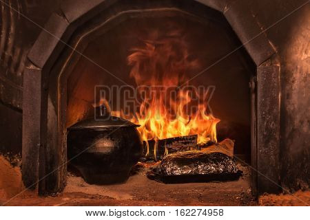 Food cooked in a cauldron in the Russian stove on fire
