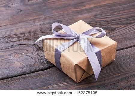 Present box on wooden surface. Ribbon bow on gift box. Template of a present.