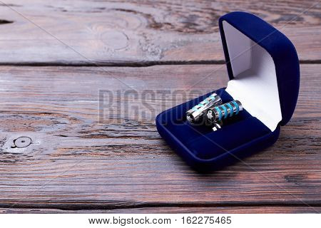 Cufflinks in velvet blue box. Case with cufflinks on wood. Formal stylish look accessory.