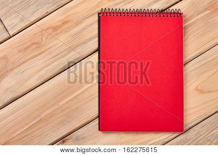 Red notebook on wooden surface. Spiral paper notepad on table. Space for doodling.
