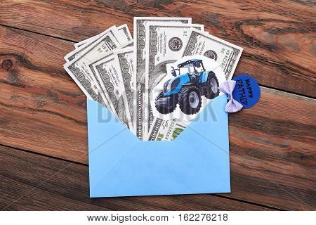 Father's Day card and money. Paper tractor on envelope. Appreciation of rural heritage.