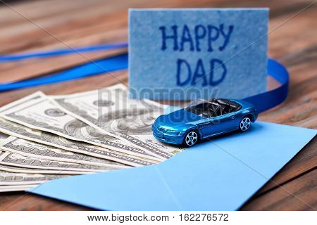 Happy Dad's card and car. Ribbon and envelope with money. Valuable gift for dad.
