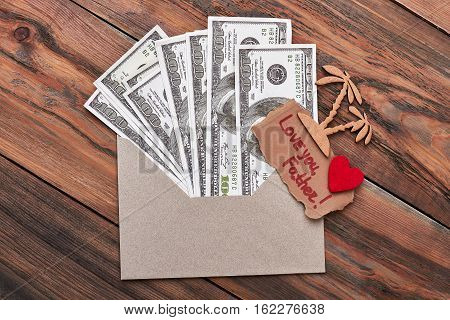 Palm and money in envelope. Love you father inscription. Memorable trip for daddy.