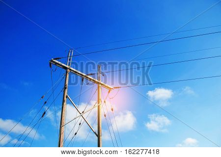 Electricity poles and wires with the blue sky.