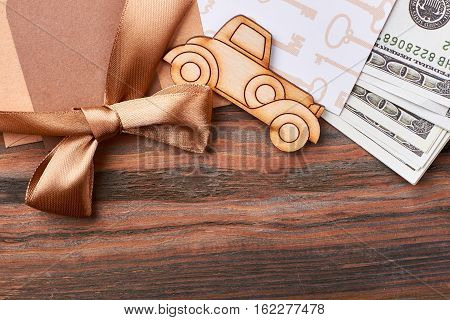 Money and ribbon bow. Pyrography car and blank paper. Posh and rich gift.