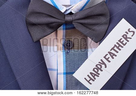Blue jacket and greeting paper. Bow tie and Father's card. Menswear for celebration.