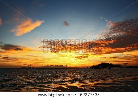 Beautiful sunset over a large sandy beach the part of Krabi province Thailand
