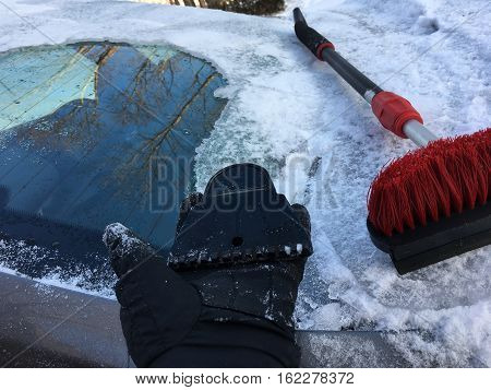 Winter driving tools for clearing car of snow and ice to avoid accident with person holding broken piece of ice scrapper and snow cleaning brush after polar vortex ice storm To avoid accident with copy space