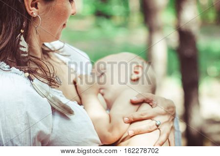 The mother feeds the young baby in the countryside in the sunlight at sunset. Breast feeding.