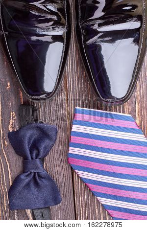 Bow tie and black shoes. Necktie and footwear. Getting ready for party.