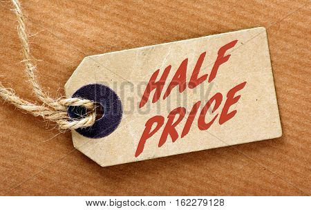 The words Half Price in red text on a luggage tag with string on a brown wrapping paper background