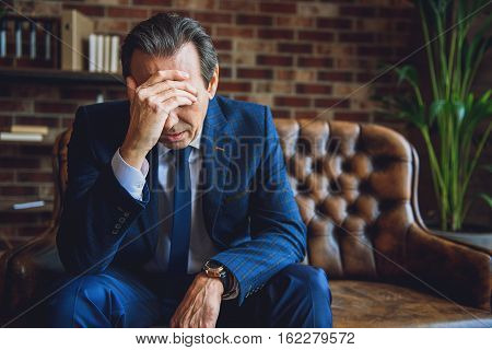 Worried mature businessman is sitting on couch. He touching his forehead with hand and closing eyes