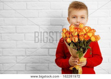 Cute boy with bouquet of beautiful flowers near light brick wall