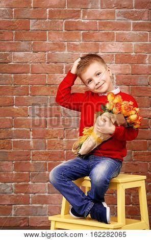 Cute boy with bouquet of beautiful flowers sitting on stool near brick wall