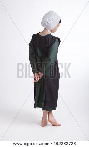 A young barefoot Amish girl in a green and black outfit isolated on a background poster