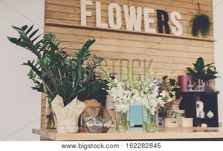 Small business. Modern flower shop interior. Floral design studio, decorations and arrangements. Flowers delivery service and sale of home plants in pots, wooden showcase, filtered image