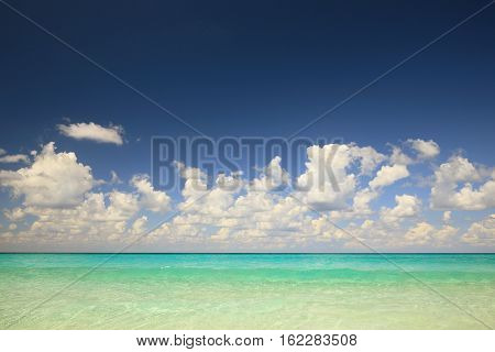 Landscape with clear water of Atlantic ocean and clouds under dark blue sky
