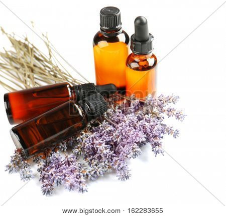 Bottles with essential oil and lavender on white background