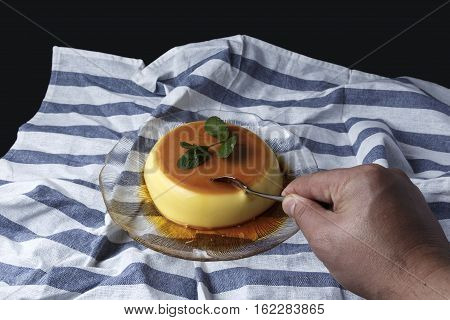 Man taking a teaspoon a piece of vanilla custard served in a glass dish on a dishcloth