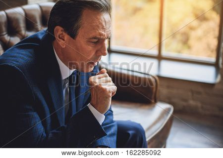 Attentive middle aged male businessperson is sitting on couch. He looking down, clenching his fist and hardly thinking